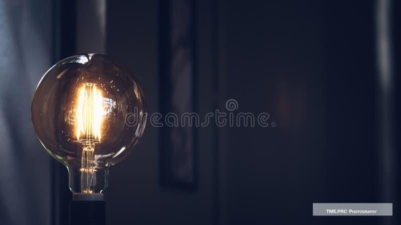 Bulbo de la luz ?mbar que brilla intensamente, vuelta realista de la imagen de la foto en bombilla del tungsteno S?mbolo de la en imagenes de archivo