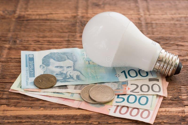Bulbo de poupança de energia do diodo emissor de luz e dinares sérvios no fundo de madeira fotografia de stock