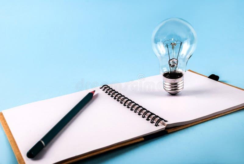 Bulbo en el cuaderno abierto aislado en un fondo azul imagenes de archivo