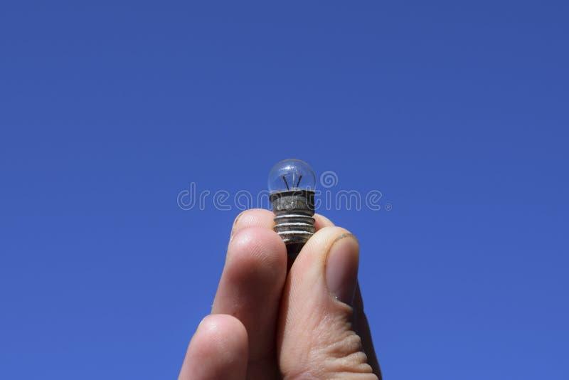 Bulbo en 3 voltios en una mano contra el cielo fotos de archivo libres de regalías