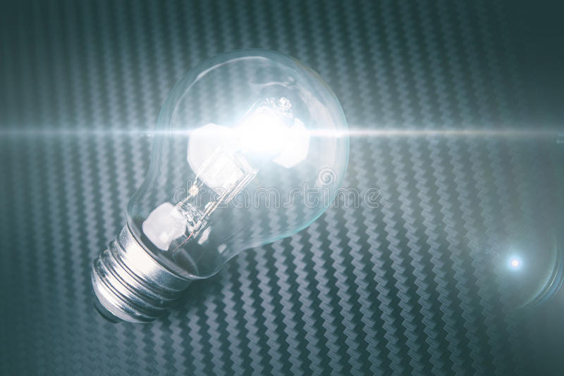 Bulbo illuminating del uno mismo en fondo del carbono Estafa de la idea de la tecnología fotos de archivo libres de regalías