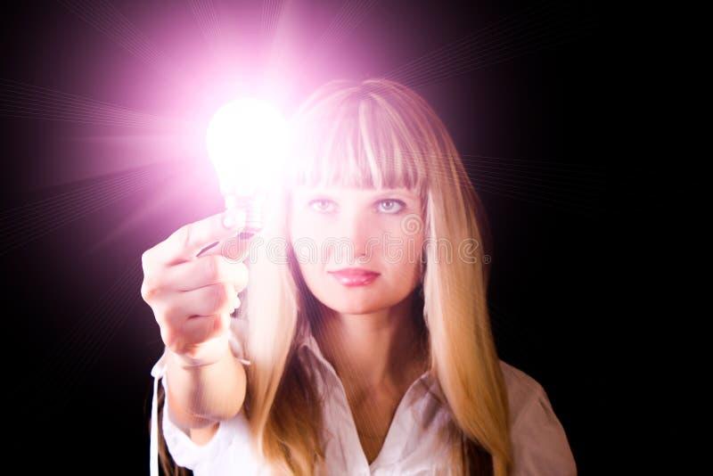 Bulbo incandescente brillante en manos de la mujer fotografía de archivo
