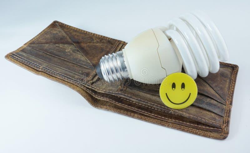 Bulbo llevado ahorro de energía con la cara feliz sonriente y el viejo wallett de cuero vacío foto de archivo