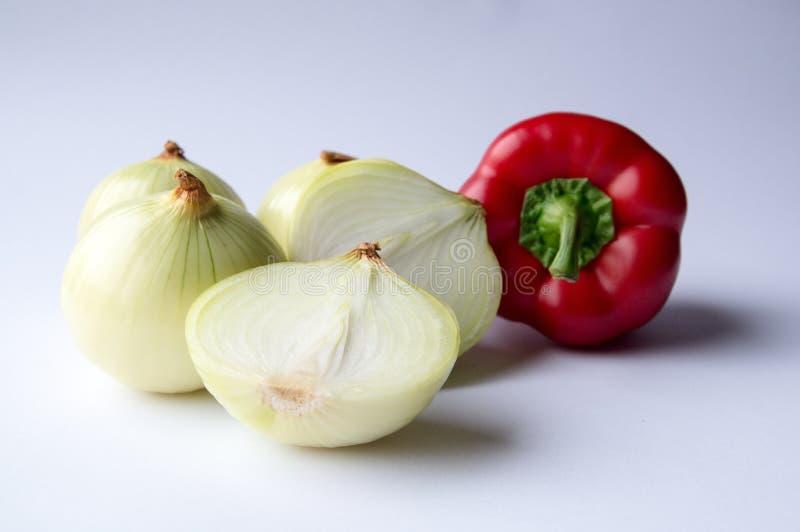 Bulbos de la cebolla blanca y pimienta roja imagen de archivo
