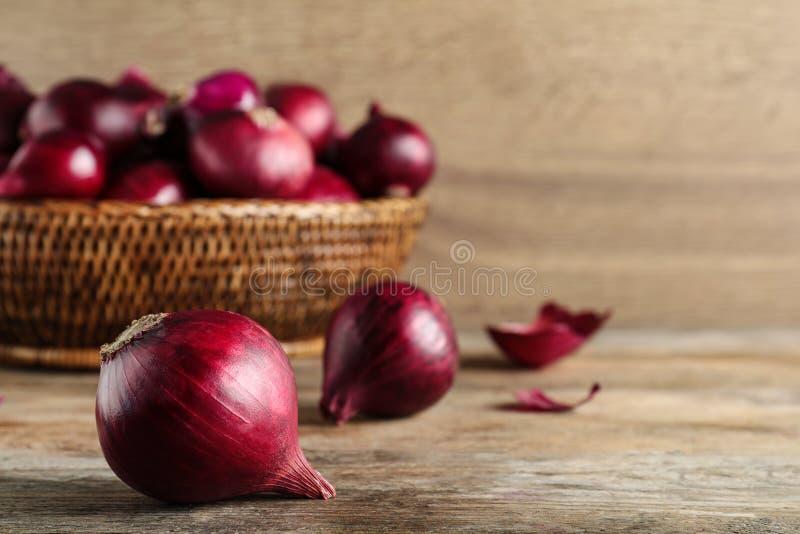 Bulbos frescos da cebola vermelha na tabela de madeira fotografia de stock royalty free