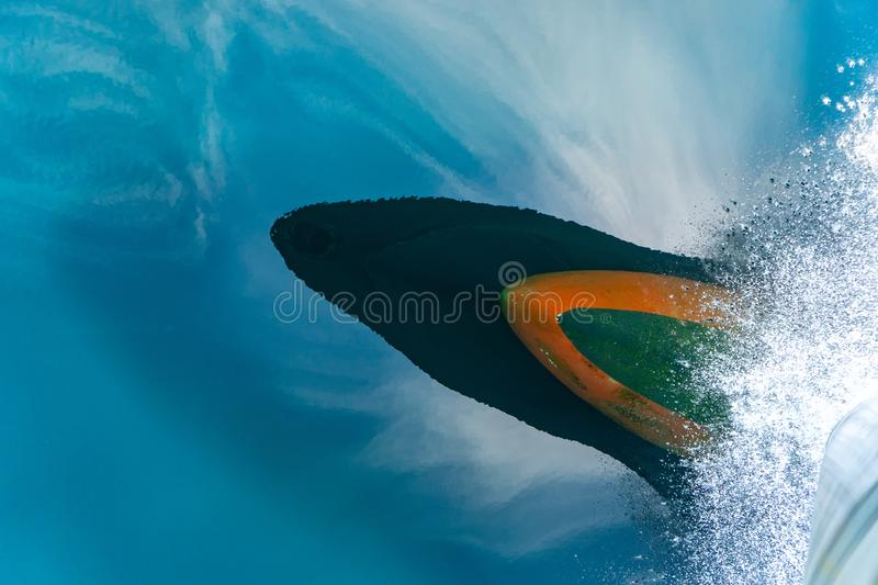 Bulbous bow of the warship sailing through the sea created wave piercing water splash with reflection of its hull and cloud above. The blue sky stock images