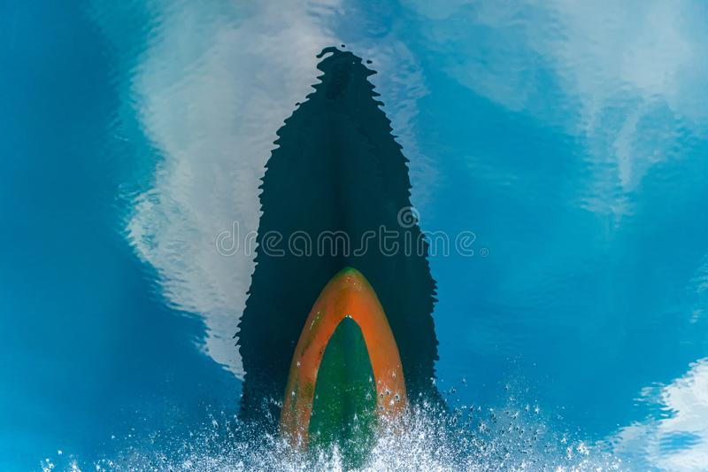 Bulbous bow of the warship sailing through the sea created wave piercing water splash with reflection of its hull and cloud above. The blue sky royalty free stock images