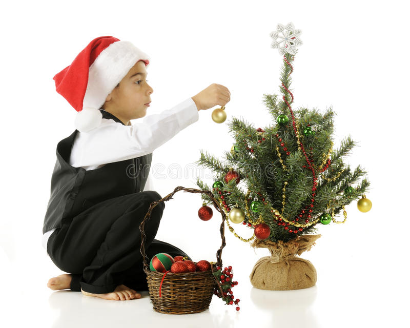 Bulbs for a Tiny Tree. A barefoot but dressed up kindergarten boy in a Santa hat decorating a tiny Christmas tree. On a white background stock photos