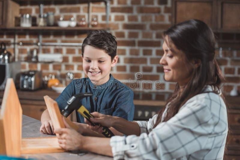 bulding一个木鸟舍的小男孩和他美丽的年轻母亲 免版税图库摄影