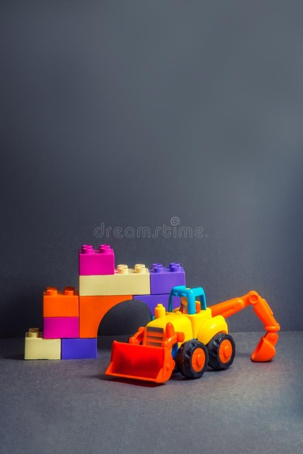 Buldozer amarelo e tijolos coloridos diferentes Carro da p? Transporte de constru??o Brinquedos para crian?as pequenas fotos de stock royalty free