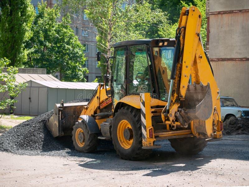 Buldozer faisant et construisant une nouvelle route goudronnée près du bâtiment civil Concepts de l'amélioration du territoire de photos stock