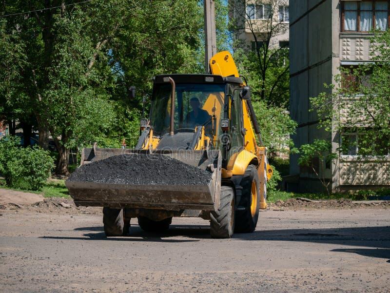 Buldozer que faz e que constrói uma estrada asfaltada nova perto do civ imagens de stock