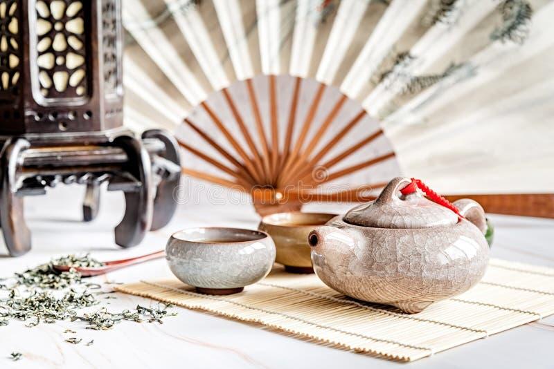 Bule asiático com as xícaras de chá no tablamat de bambu decorado com fã chinês, lanterna e chá verde dispersado no mármore branc fotos de stock royalty free