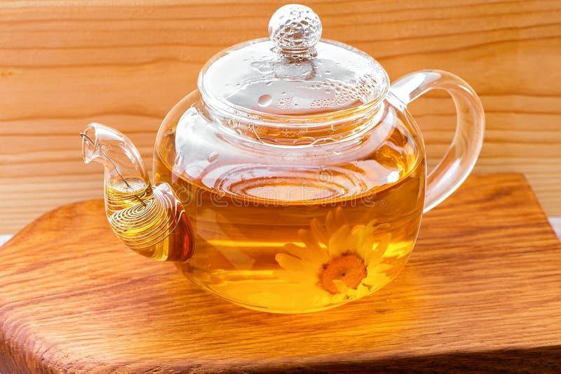 Bule de vidro com chá de camomila herbal fechado sobre fundo de prato de madeira imagens de stock royalty free
