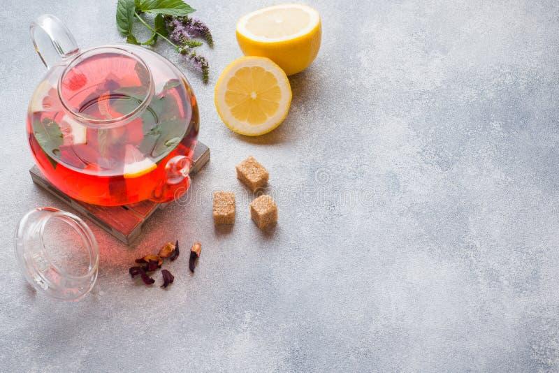Bule de vidro com chá, hortelã e limão na tabela cinzenta com espaço da cópia foto de stock