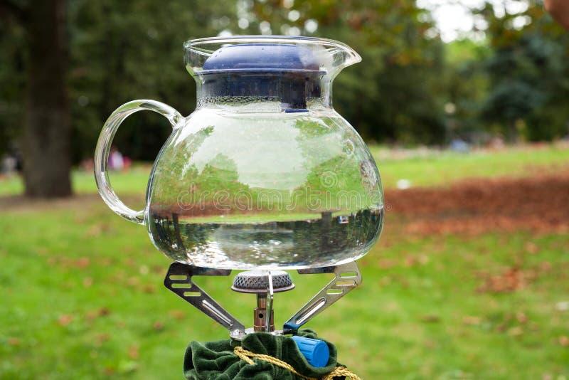 Bule de vidro em um queimador de gás no fundo da natureza imagens de stock royalty free