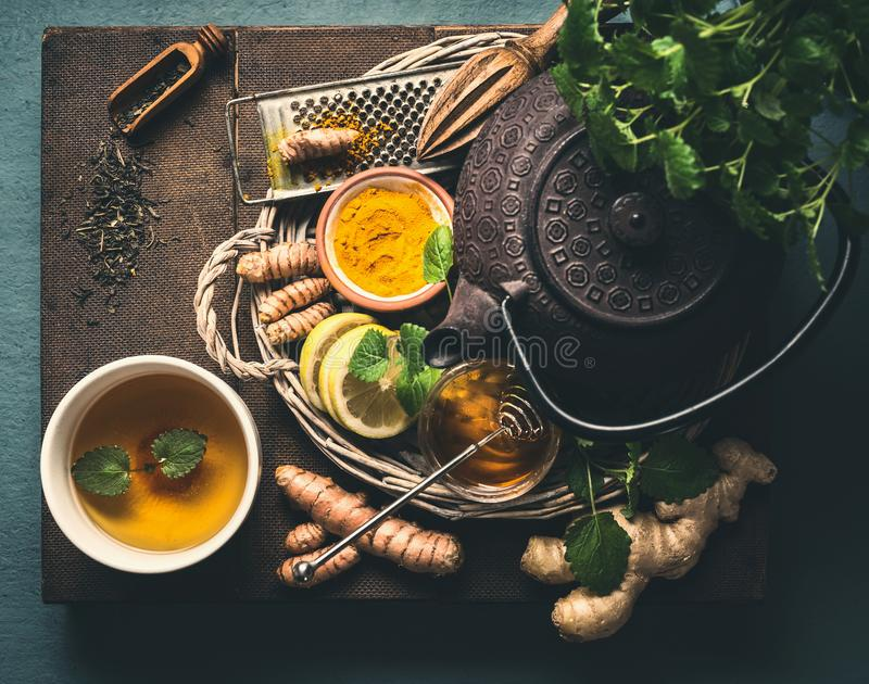Bule do ferro com os ingredientes ervais frescos para o chá saudável do gengibre da cúrcuma com limão e copo do chá dourado da cú imagem de stock