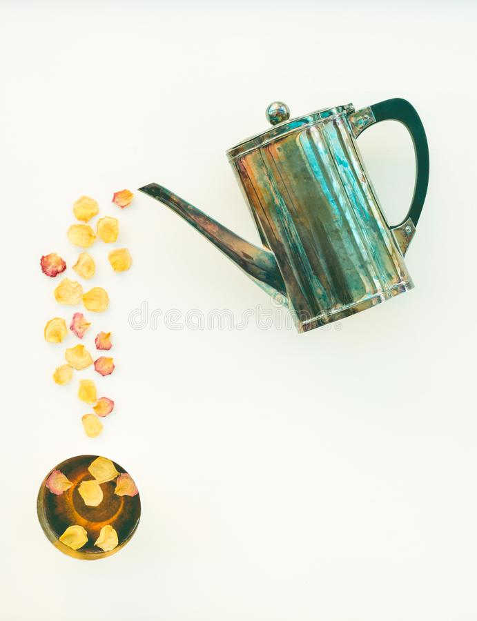 Bule do vintage e copo do chá com pétalas cor-de-rosa imagem de stock
