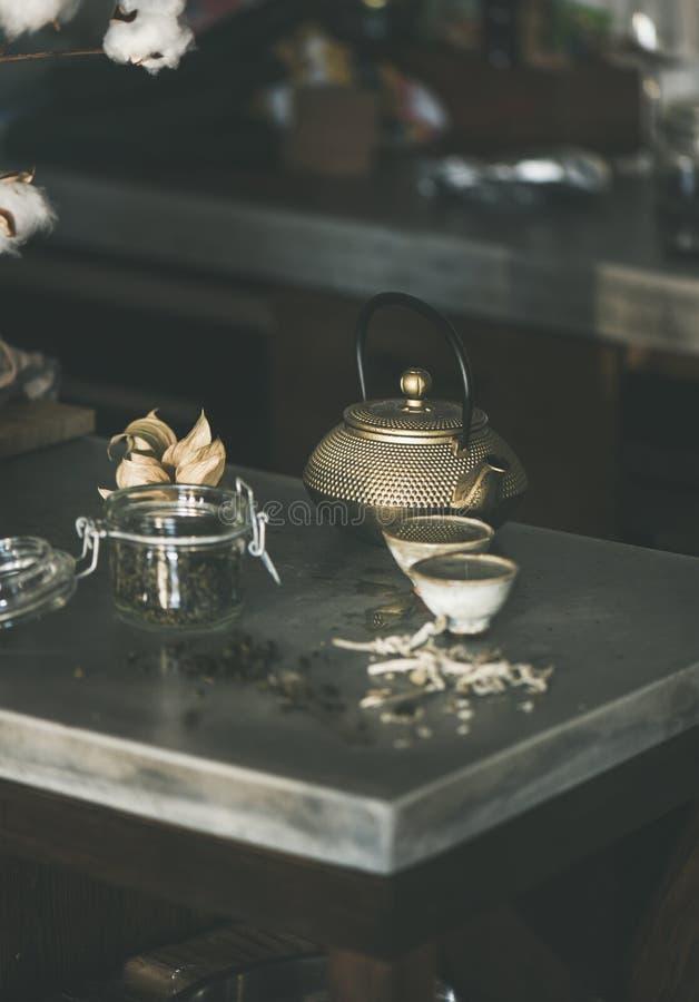 Bule dourado do ferro e copos japoneses completos do chá verde imagens de stock royalty free