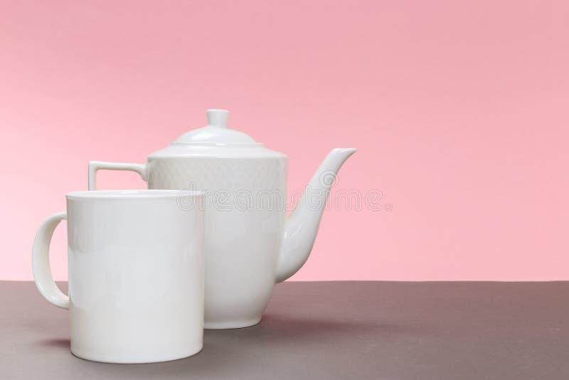 Bule e copo brancos da porcelana do vintage em uma placa cinzenta e em um fundo cor-de-rosa imagens de stock