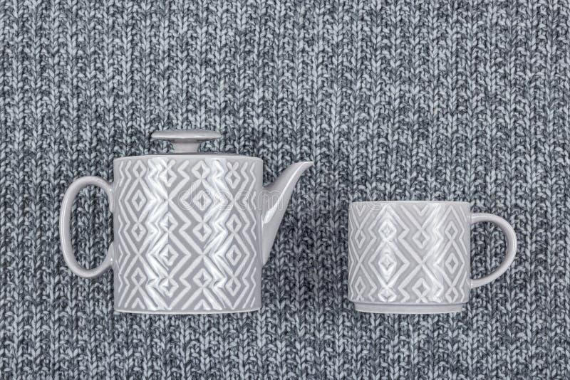 Bule e copo cerâmicos no fundo cinzento de lãs fotografia de stock royalty free