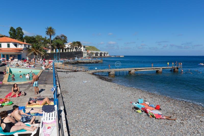 Bulevar y playa con la gente que toma el sol y que nada el desconocido en Madeira, Portugal fotos de archivo