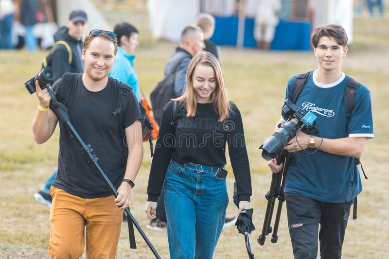 BULGAR, RUSSIA 11-08-2019: A photographer team of two men and woman walking on the medieval festival and carrying the royalty free stock images