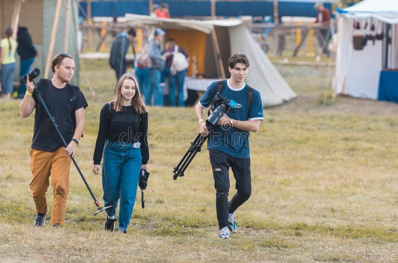 BULGAR, RUSSIA 11-08-2019: A photographer team walking on the medieval festival and carrying the equipment royalty free stock photo