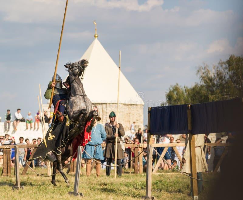 Bulgare, Fédération de Russie - août 2018, - un homme dans l'armure du ` s de chevalier montant un cheval qui a soulevé son sabot photo libre de droits