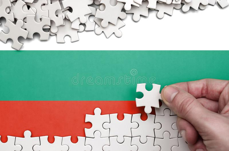 Bulgaria flag is depicted on a table on which the human hand folds a puzzle of white color royalty free stock photography