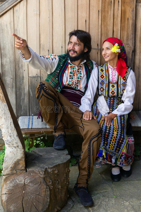 Bulgarian costumes. Young happy couple sitting in traditional Bulgarian costume royalty free stock image