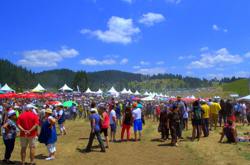 Bulgarian National Fair thousands participants. Mountain meadow packed with thousands of people communicating ,listening folklore music,relaxing and having meal royalty free stock photos