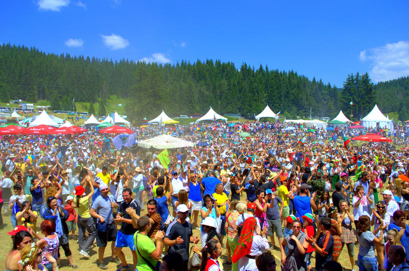 Bulgarian National Fair thousands participants. Mountain meadow packed with thousands of people istening and applauding folklore music concert ,communicating royalty free stock images