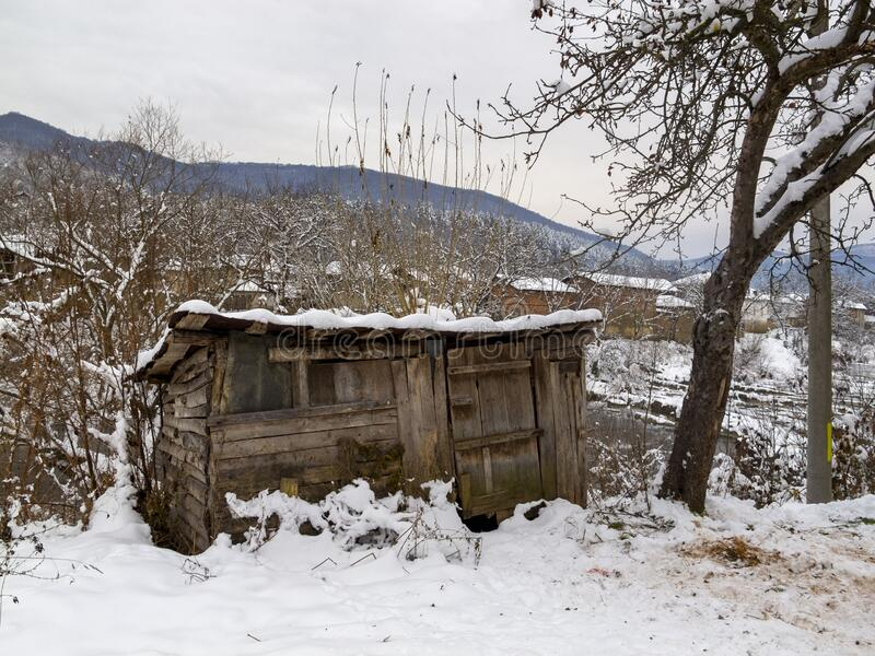 Bulgarian winter village view. Old wooden log shed at the Vidima riverbank at the winter Bulgarian Fore-Balkan village of Debnevo, Central-North Bulgaria stock photo