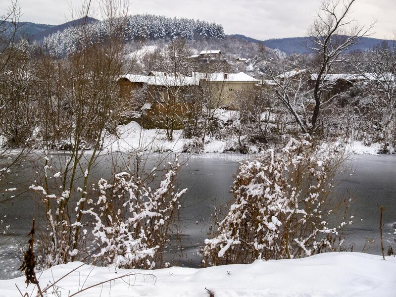 Bulgarian winter village view. Picturesque snowy rural view of the frozen Vidima River and riverbank houses at the Bulgarian Fore-Balkan village of Debnevo royalty free stock images