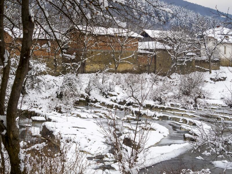 Bulgarian winter village view. Picturesque snowy rural view of the frozen Vidima River and riverbank houses at the Bulgarian Fore-Balkan village of Debnevo stock photography