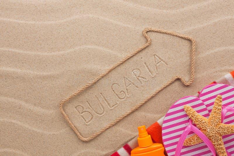 Bulgarienpekare- och strandtillbehör som ligger på sanden arkivbilder