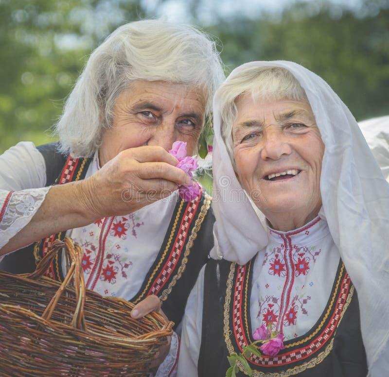 Bulgariska damer som väljer rosa kronblad royaltyfri fotografi