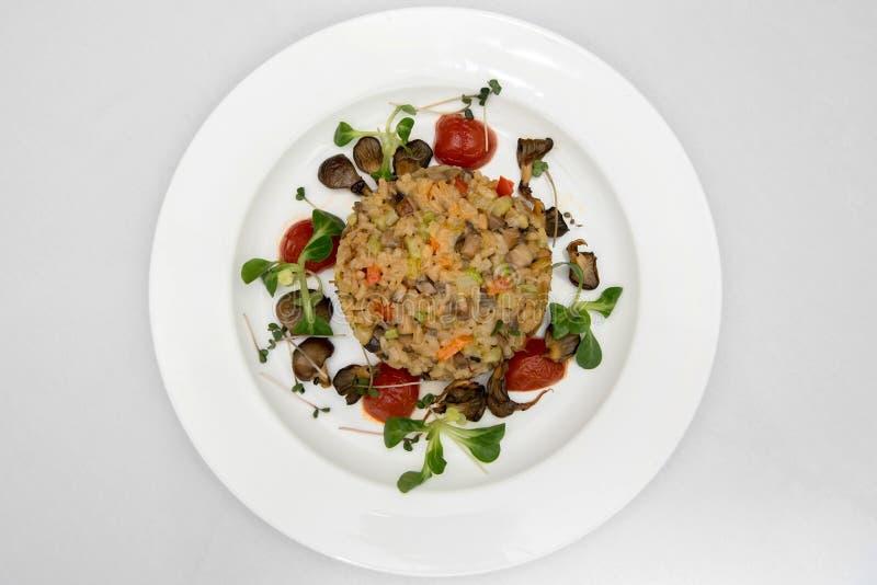 Bulgur com cogumelos e verdes em uma placa branca em um restaurante fotografia de stock