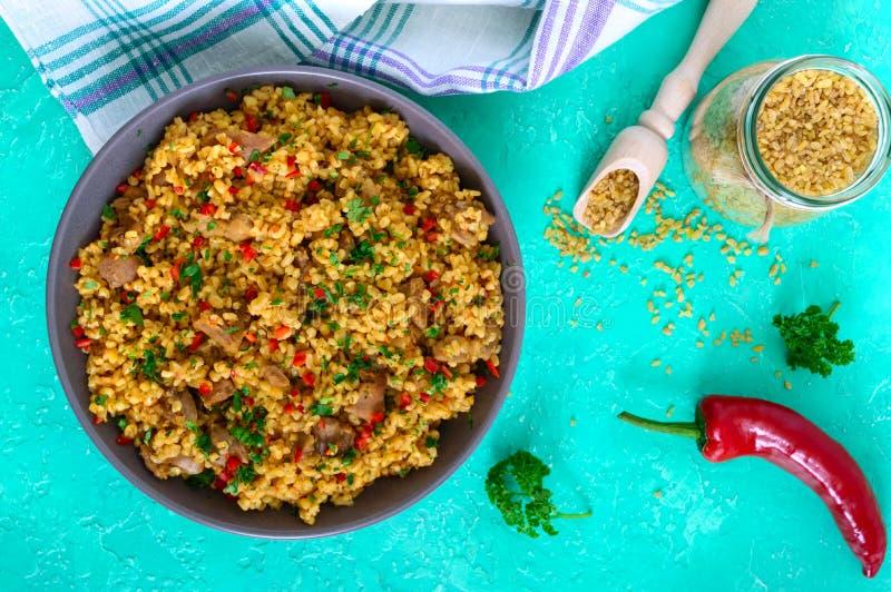 Bulgur met kip en groenten Heerlijke gezonde warme salade op een heldere achtergrond Bulgur pilau stock foto's