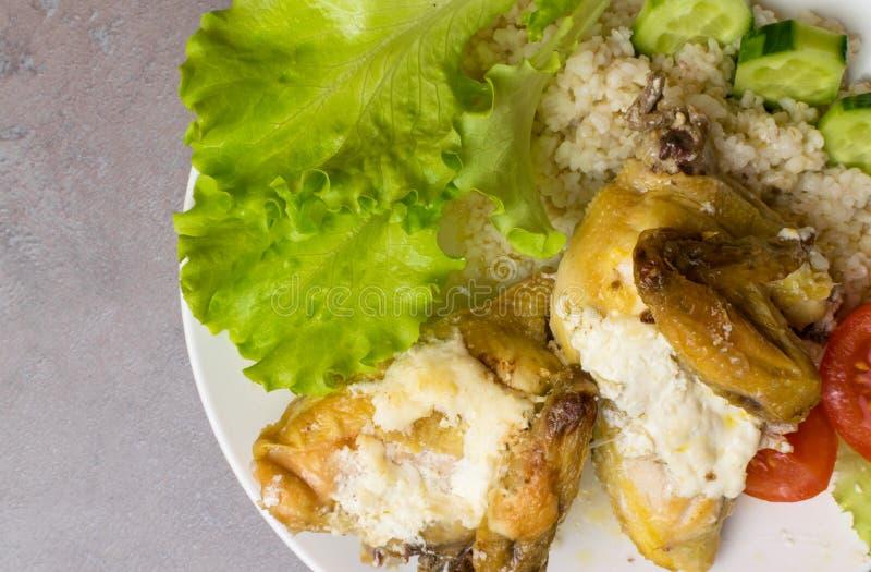 Bulgur met kip, ruwe tomaten, salade in een witte plaat Hoekmening over rustieke concrete grijze achtergrond stock afbeelding
