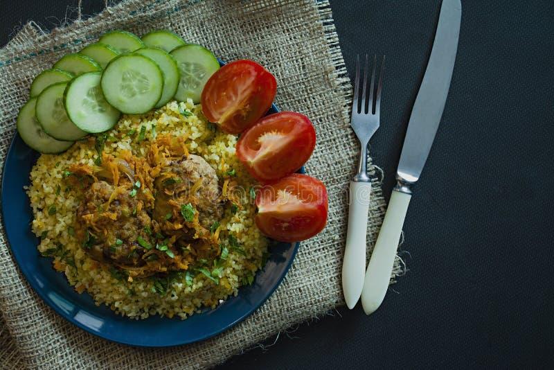 Bulgur mit Kotelett und Gem?se diente auf einer Platte Schweinefleischkoteletts mit Brei Richtige Nahrung Dunkler Hintergrund Ans stockfotos