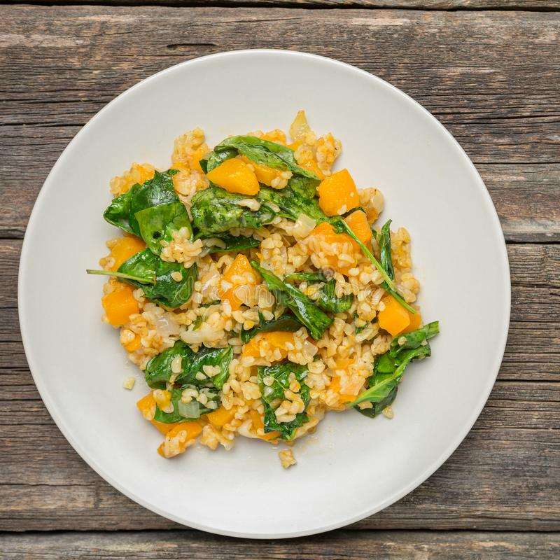 Bulgur with Vegetables- healthy homemade organic vegan vegetarian diet food. Bulgur with Vegetables:pumpkin, onion and spinach on wooden background - healthy stock photography
