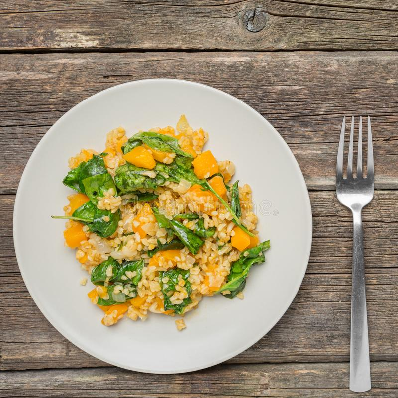 Bulgur with Vegetables- healthy homemade organic vegan vegetarian diet food. Bulgur with Vegetables:pumpkin, onion and spinach on wooden background - healthy royalty free stock photography