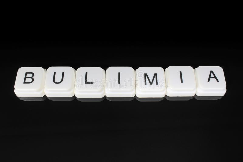 Bulimia, ext word title caption label cover backdrop background. Alphabet letter toy blocks on black reflective. Bulimia text word title caption label cover stock photography