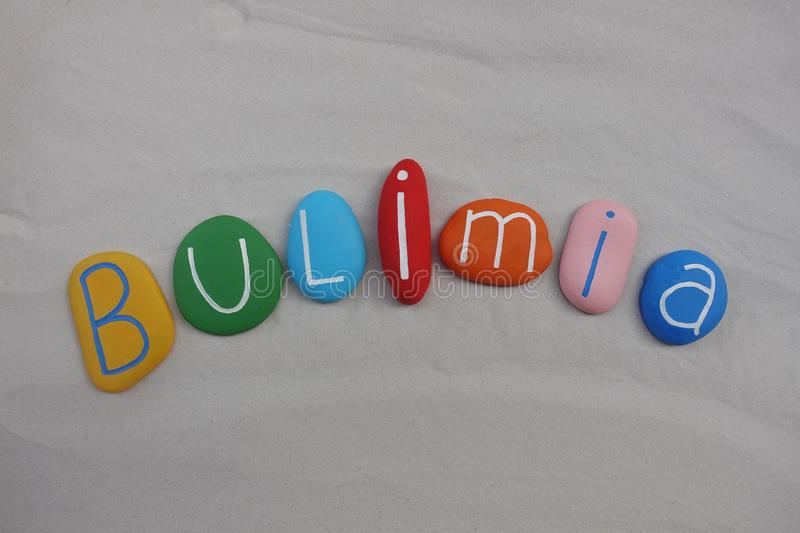 Bulimia illness text with colored stones over white sand. Bulimia word composed with colored and carved stones over white sand stock photo