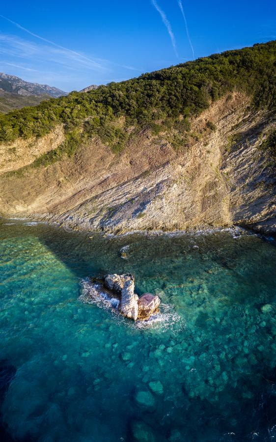 Aerial view of Buljarica promontory, steep cliff on the coast lapped by Adriatic sea. Petrovac, Montenegro. Aerial view of Buljarica promontory, steep cliff on royalty free stock photos