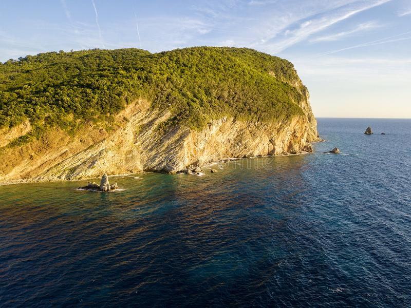 Aerial view of Buljarica promontory, steep cliff on the coast lapped by Adriatic sea. Petrovac, Montenegro. Aerial view of Buljarica promontory, steep cliff on stock photos