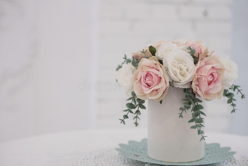 Bulk artificial flowers in a round box are on the table stock photo
