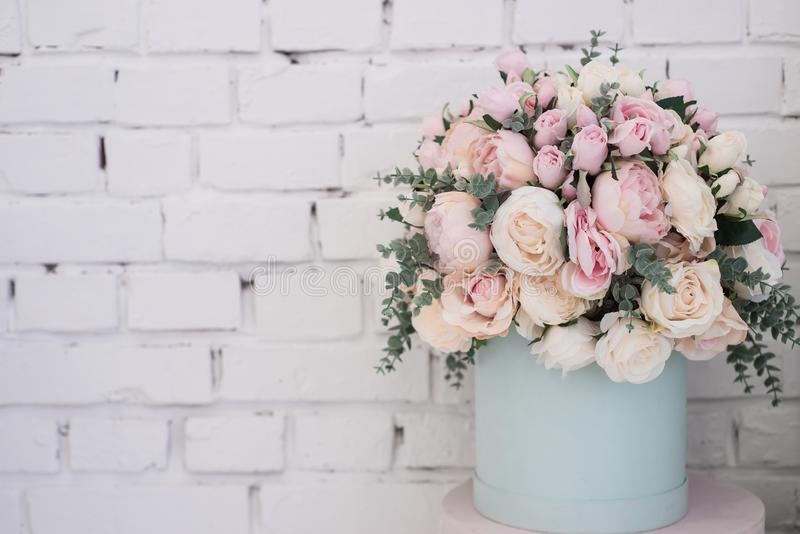 Bulk artificial flowers in a round box on a white brick wall background royalty free stock image